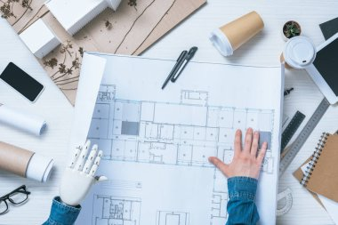 partial view of male architect with prosthetic arm looking at blueprint