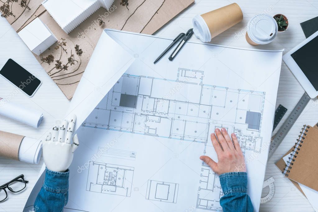 Cropped image of male architect with prosthetic arm working with blueprint at table with smartphone and model of house stock vector