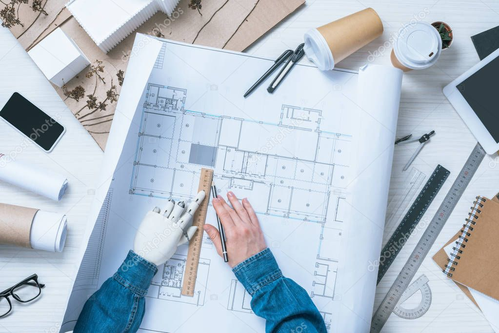 Cropped image of male architect with prosthetic arm drawing on blueprint at table stock vector