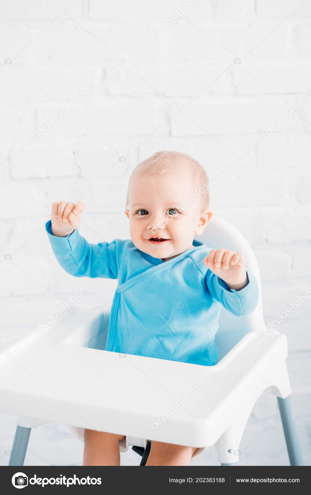 adorable little baby sitting high chair front white brick wall