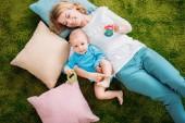 Hohe Ansicht von glücklicher Mutter und Kind auf grünem Teppich liegend mit Kissen zu Hause