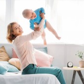 happy mother raising up laughing little child while sitting on bed at home