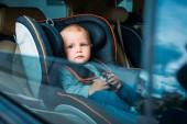 Sladké dítě sedící v dětské autosedačky v autě a při pohledu přes okno