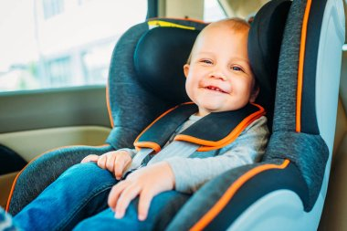 happy little baby sitting in child safety seat in car and looking at camera