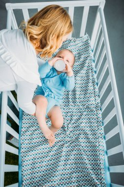 high angle view of mother putting her little child into crib at home
