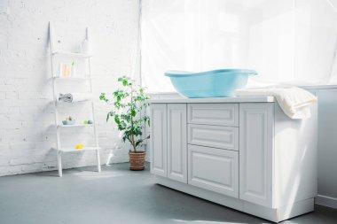 Blue plastic childrens bathtub on stand in white modern room stock vector