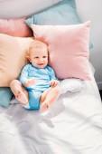 pohled z vysokého úhlu smát malé dítě ležet v posteli
