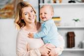matka nosí roztomilé malé dítě a při pohledu na fotoaparát doma
