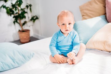 adorable little baby sitting on bed at home and looking at camera