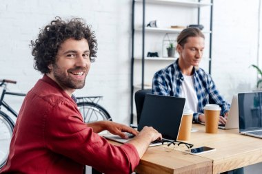 young man using laptop with blank screen and smiling at camera while working with colleague in office