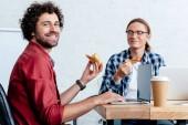 Fotografie lächelnde junge Männer essen Pizza und Laptops im Büro