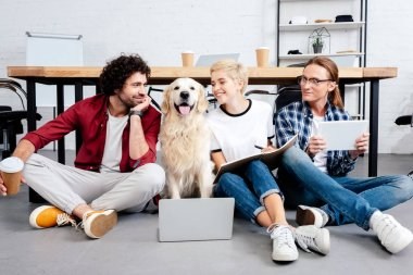 young business colleagues using digital devices and looking at dog in office