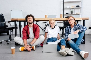 smiling young start up team sitting on floor and working together