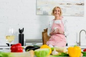 Fotografie smiling beautiful senior woman sitting on kitchen counter with cup of tea and looking at camera