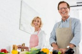 Fotografie nízký úhel pohled šťastný starší pár společné vaření v kuchyni a při pohledu na fotoaparát
