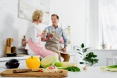 Fotografia vista ravvicinata della verdura fresca nel tagliere di legno e coppie senior bere vino dietro in cucina