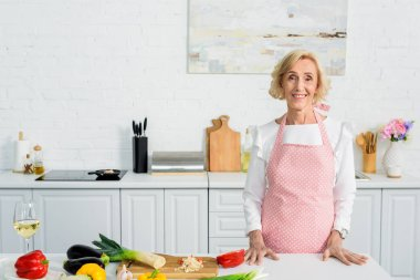 smiling attractive senior woman standing at kitchen counter and looking at camera