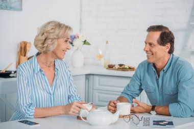 happy senior couple smiling each other and talking while drinking tea together at home