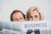 Fotografie senior couple holding business newspaper and looking at camera