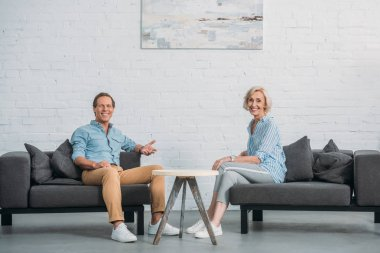 happy elderly couple smiling at camera while sitting together in cozy room
