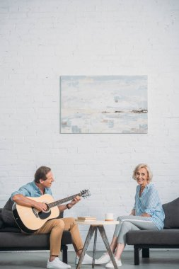 happy man playing acoustic guitar and looking at senior wife smiling at camera at home