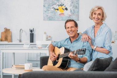 happy senior couple smiling at camera while man playing guitar at home