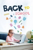 Fotografie Adorable kid in eyeglasses smiling at camera while studying with laptop at home with icons and back to school lettering