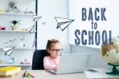 Gyönyörű vörös hajú iskolás használ laptop, miközben tanul otthon Papírrepülők és a vissza az iskolába felirat