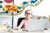 Átgondolt kis iskolás a szemüvegek keresi fel ülő-on iskolapad és laptop használata idő a tudás felirat