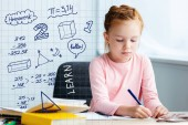 Fotografie adorable red haired schoolgirl sitting at desk and studying at home with math icons