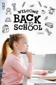 Fényképek side view of thoughtful schoolgirl holding pen and looking away while studying at home, icons and back to school lettering