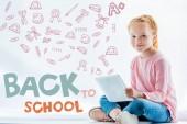 krásná rusovláska dítě pomocí digitálního tablet, s ikonami a zpět do koncepce školy