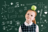 Photo pensive little red haired schoolgirl with apple on head standing near chalkboard with school icons