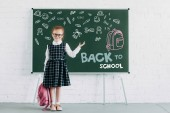 Fotografie adorable little schoolgirl with backpack showing blackboard with icons and back to school lettering