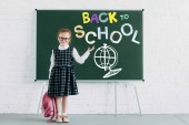 Fotografie adorable little schoolgirl with backpack showing blackboard with back to school lettering