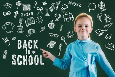 Beautiful smiling red haired schoolgirl pointing at chalkboard with icons and back to school lettering stock vector