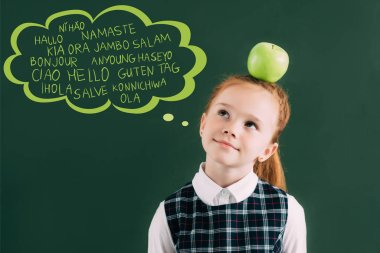 pensive little red haired schoolgirl with apple on head standing near chalkboard with words on different languages in speech bubble