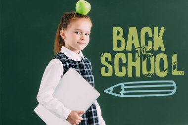 beautiful little schoolgirl with apple on head holding laptop and standing near blackboard with back to school lettering