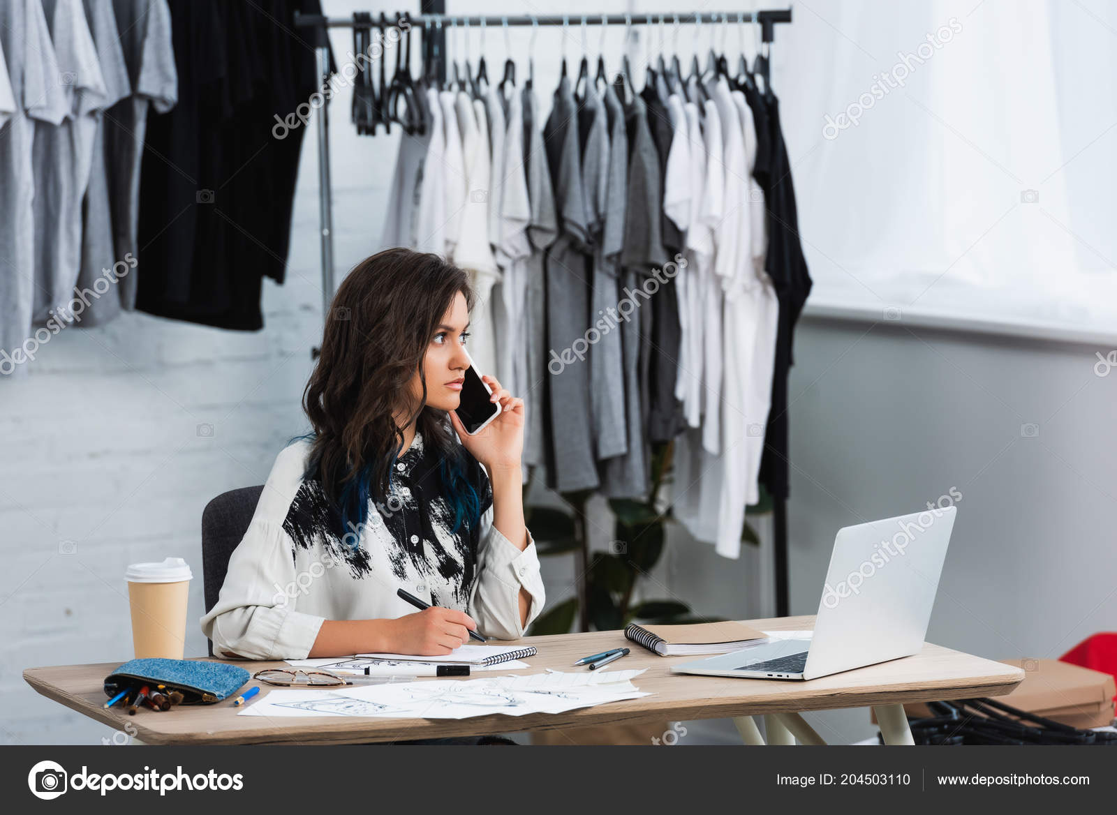 9c4e57fd5d7e0 Designer de moda feminina jovem falando no smartphone na mesa de trabalho e  olhando para longe no estúdio de design de vestuário — Fotografia por ...