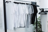 selective focus of white, black and grey empty t-shirts on hangers in clothing design studio