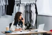 fiatal női divat tervező beszélő smartphone dolgozó asztal, és keres el ruházat design Studio