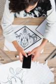 Fotografia vista ambientale della stilista femminile che cattura maschera della pittura per la stampa su t-shirt al tavolo