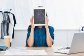 mladá žena pokrývající tvář ipad tabletu u stolu