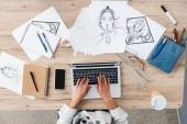 Fotografie oříznutý obraz ženské Designer pomocí přenosného počítače u stolu s obrazy a smartphone