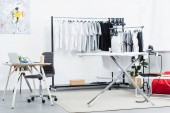 Fotografie selective focus of t-shirts on hangers, table with laptop and ironing board in clothing design studio