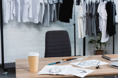 selective focus of coffee cup and paintings on working table in clothing design studio