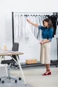 Photo smiling female fashion designer holding white t-shirt in clothing design studio