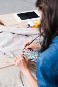 Fotografie weibliche Mode-Designer Malerei auf Jacke am Arbeitstisch in Kleidung Design-studio