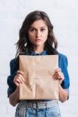 Selektivní fokus mladá žena držící papírovém balení před cihlová zeď