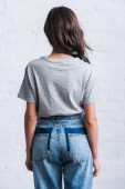 Fotografie rear view of young woman in empty grey t-shirt in front of brick wall